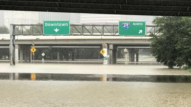 Una calle inundada bajo el letrero de Downtown.