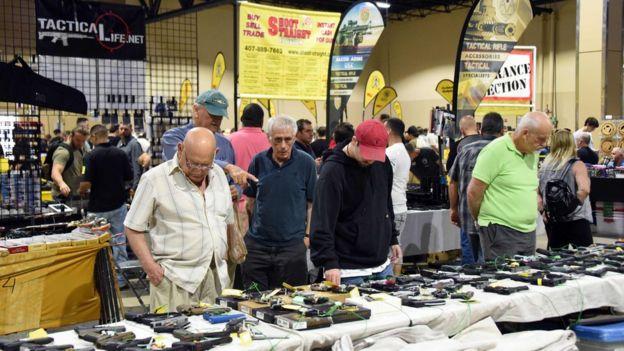 Homens observam armas expostas na Flórida Gun Show