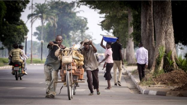 Men pushing a heavily laden bicycle on the streets of Kananga
