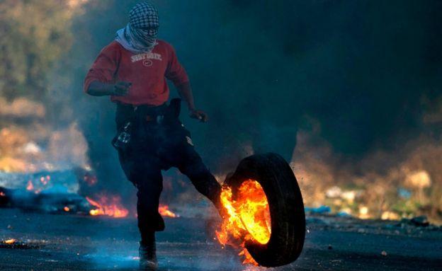 Un manifestante palestino lanza un neumático en llamas hacia las fuerzas israelíes.