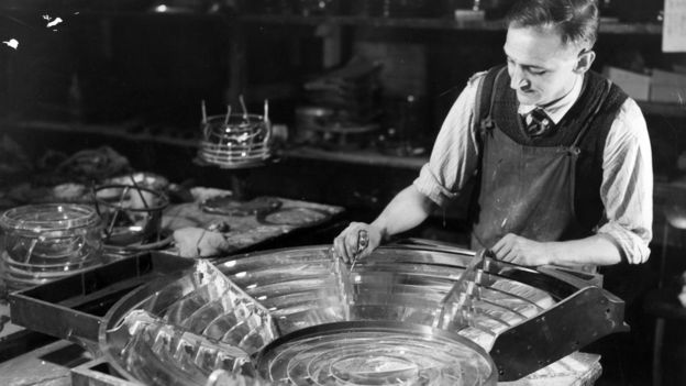 A worker making the glass prisms for the lighthouses