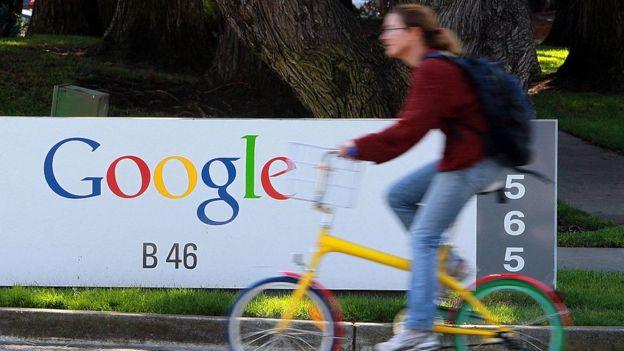 Mujer pasa en bicicleta frente a un cartel que dice Google.