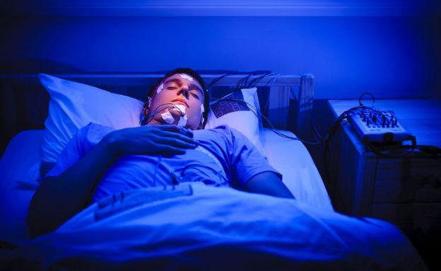 Hombre con electrodos conectados a la cara y la cabeza mientras duerme