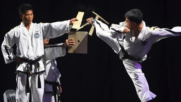 A man kicks through a wooden board during a taekwondo demonstration