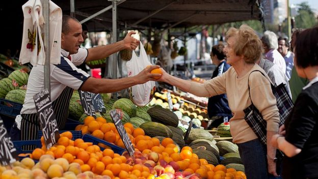 Mujer comprando naranjas