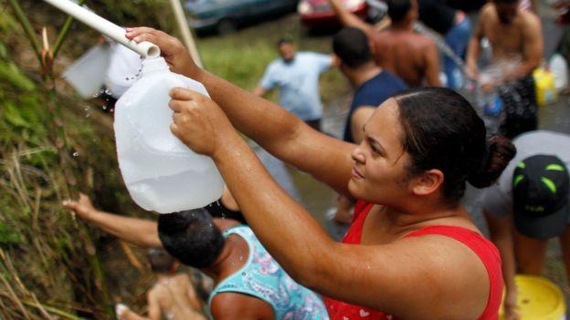 Una mujer en el oeste de San Juan rellena un envase desde una fuente natural ante la escasez de agua potable.