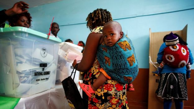 Women carrying babies cast their vote in Gatundu in Kiambu county, Kenya, 8 August