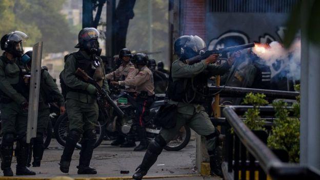 Policía disparando.