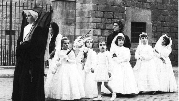Una monja guía a un grupo de niñas vestidas de blanco para su primera comunión.