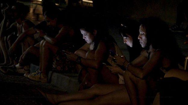 Jóvenes en uno de los puntos para el acceso a internet en la isla.