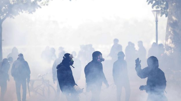 Protesters wear protective masks against tear gas in clashes with French police forces during a demonstration of workers