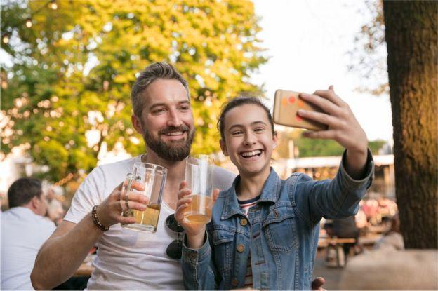 Niñá se toma un selfie con un adulto mientras ambos sostienen un vaso de cerveza.