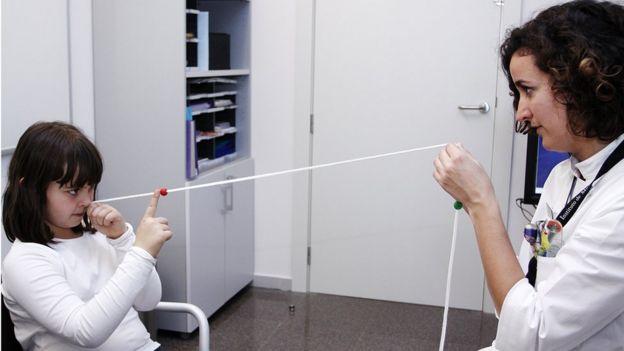 Niña y optometrista haciendo un ejercicio de terapia visual