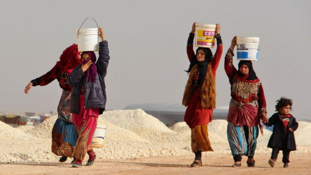 Mujeres siria desplazadas cargando agua