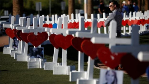 A man looks at the 58 white crosses displayed for the victims of the Route 91 music festival shooting in Las Vegas, Nevada.