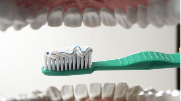 Cepillo de dientes a punto de entrar en la boca.