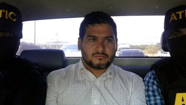 Roberto Castillo in the back of a car after his arrest, flanked by two officers