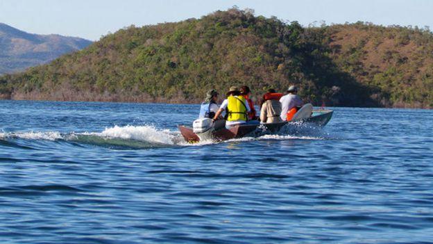 Investigadores em uma lancha em um lago na Serra da Mesa, Brasil