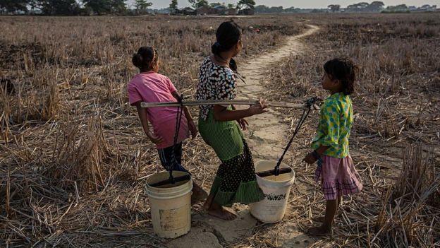 Una mujer con dos niños en una zona rural de Birmania.