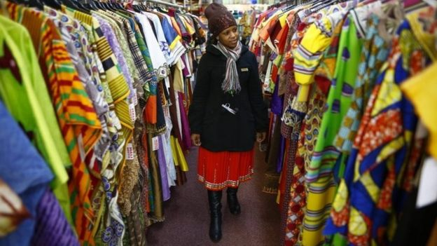 Woman looks at rails of African clothing