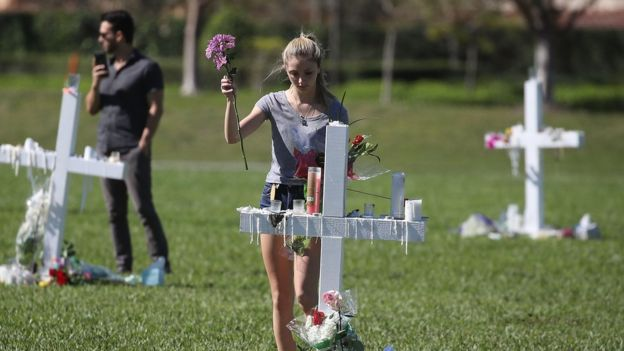 A young women places flowers at a memorial site that honours victims of the mass shooting at Marjory Stoneman Douglas High School, at Pine Trail Park on February 16, 2018 in Parkland, Florida