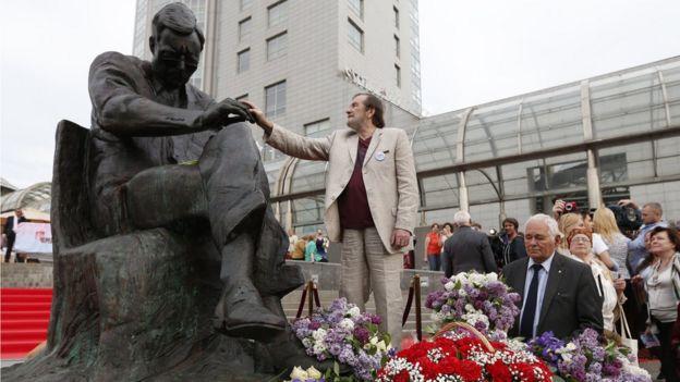 Максим Д. Шостакович стоит около памятника своему отцу Дмитрию Шостаковичу. 2015 год