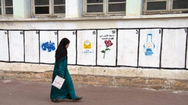 Woman walks past party symbols on a wall in Rabat, 7 October 2016