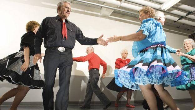 Personas bailando en grupo intercambiando parejas en un círculo