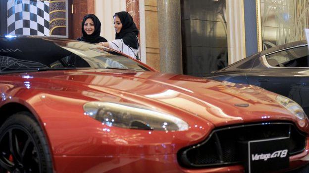 Mujeres sauditas miran un automóvil a la venta.