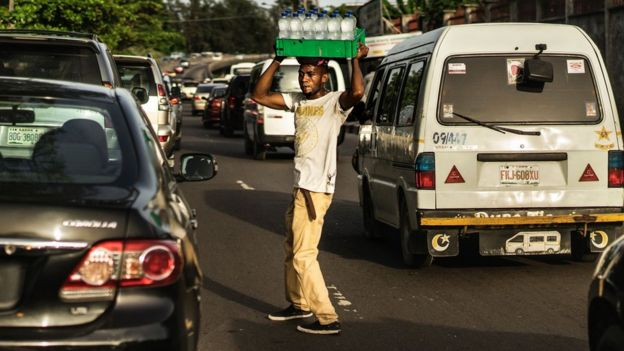 Male sells water in the middle of a busy road in Lagos