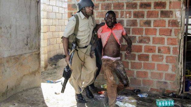 A Zambian policeman arresting a rioter in Lusaka - April 2016
