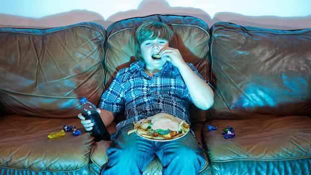 Child eating a large plate of food sitting in front of the television