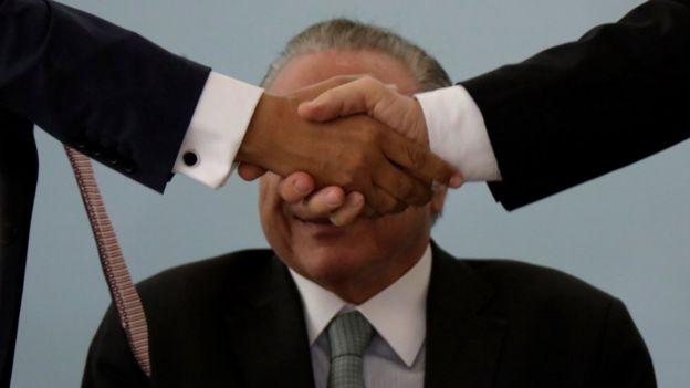 Aperto de mão cobre o rosto do presidente Michel Temer