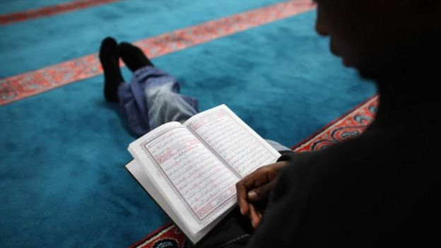 A Muslim man reads the Koran before Iftar