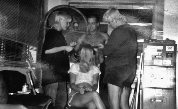 Angela, right, shaving the head of a girl dating a skinhead in her group