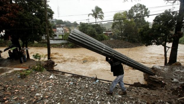 A man recovers some zinc sheets after a mudslide damaged their homes during heavy rains by Tropical Storm Nate in San Jose, Costa Rica October 5, 2017