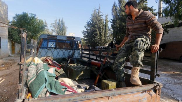Syrian rebel fighter sits on a pick-up truck in Kafr Nabudeh, Hama province (11 October 2015)