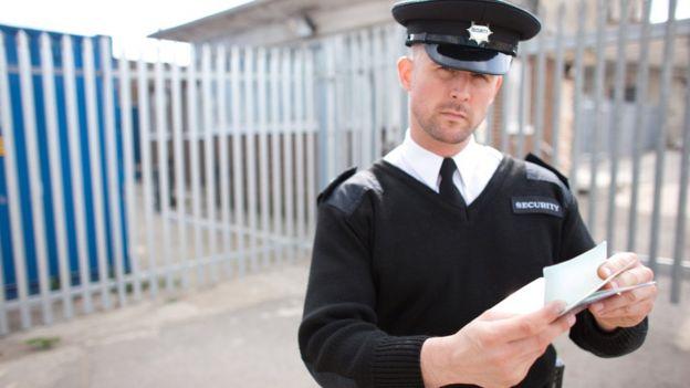 Agente de policía revisando pasaporte y mirando sospechosamente.