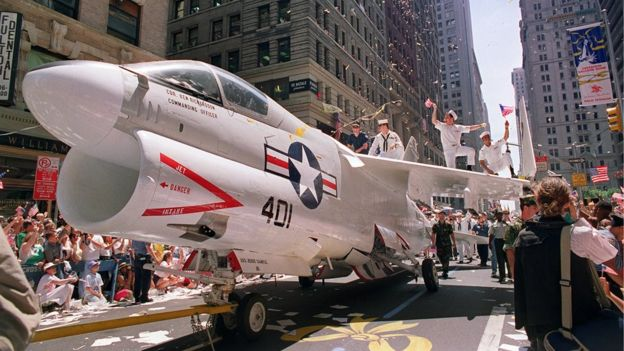 A Navy A-7 Corsair jet is pulled down Broadway Avenue as sailors rejoice on the wings during the Operation Welcome Home ticker-tape parade during the 10 June 1991 celebration for returning Gulf War troops