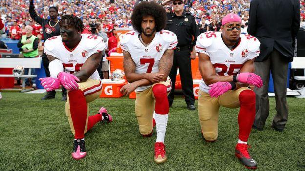 Colin Kaepernick y dos compañeros de rodillas durante la entonación del himno en San Francisco