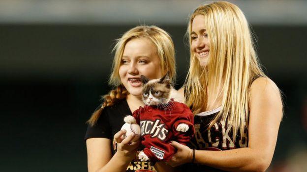 Grumpy cat con una camiseta de baseball, en Arizona, en 2015, con sus dueña, Tabatha Bundesen (derecha).