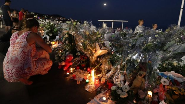 People light candles at a makeshift memorial on the Promenade des Anglais in Nice on July 19, 2016