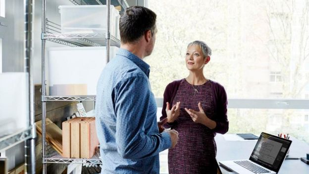 Dos personas hablando en una oficina