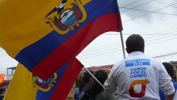 Hombre sostiene una bandera de Ecuador durante la campaña presidencial.