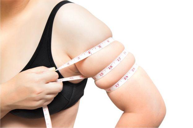 Mujer midiéndose las dimensiones del brazo.