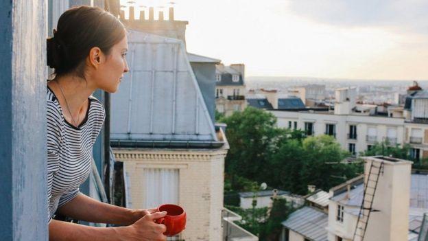 mulher tomando café na janela
