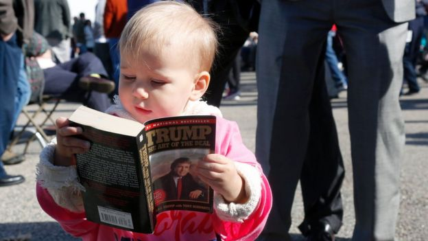 Grace Mahoney, 16 months, looks at a copy of 'The Art of the Deal' before the start of an event with Republican presidential candidate Donald Trump on October 15, 2016 in Portsmouth, New Hampshire.