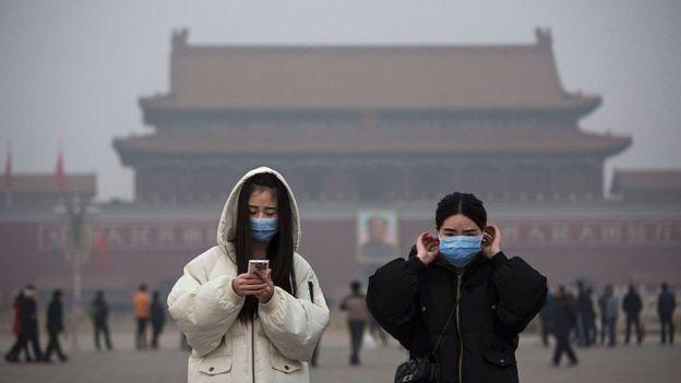 Mujeres con máscaras en Pekín.