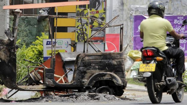 A Sri Lankan man rides his bicycle past a burnt vehicle a day after anti-muslim riots erupted in Digana, a suburb of Kandy on March 7, 2018. Sri Lanka on March 5 declared a nationwide state of emergency to quell anti-Muslim riots that have killed at least two people and damaged dozens of mosques and homes, a minister said. 'The cabinet of ministers decided on tough measures, including a 10-day nationwide state of emergency,' Minister of City Planning Rauff Hakeem said as police imposed a curfew in the riot-hit central district of Kandy. / AFP PHOTO / STR (Photo credit should read STR/AFP/Getty Images)