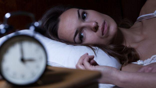 Mujer acostada y despierta.